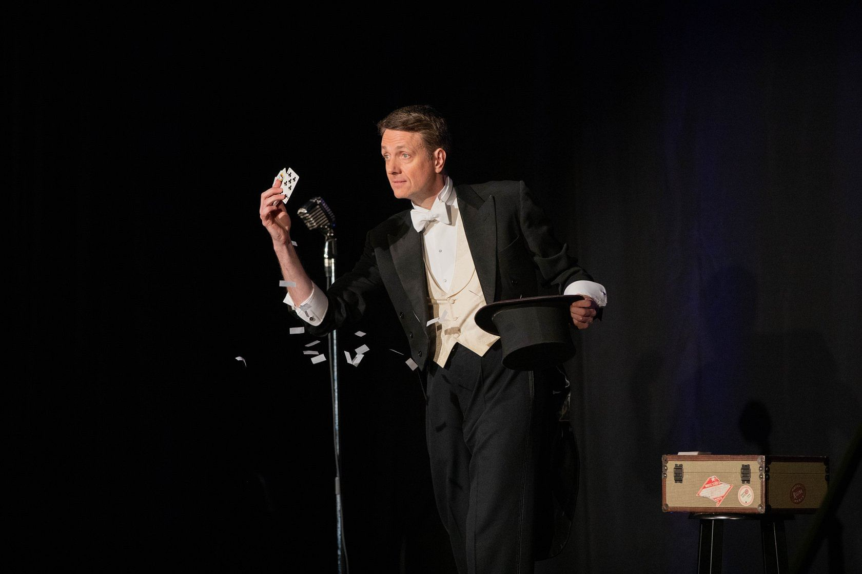 Magician in tuxedo performs a card trick at the Magifest Magic Convention