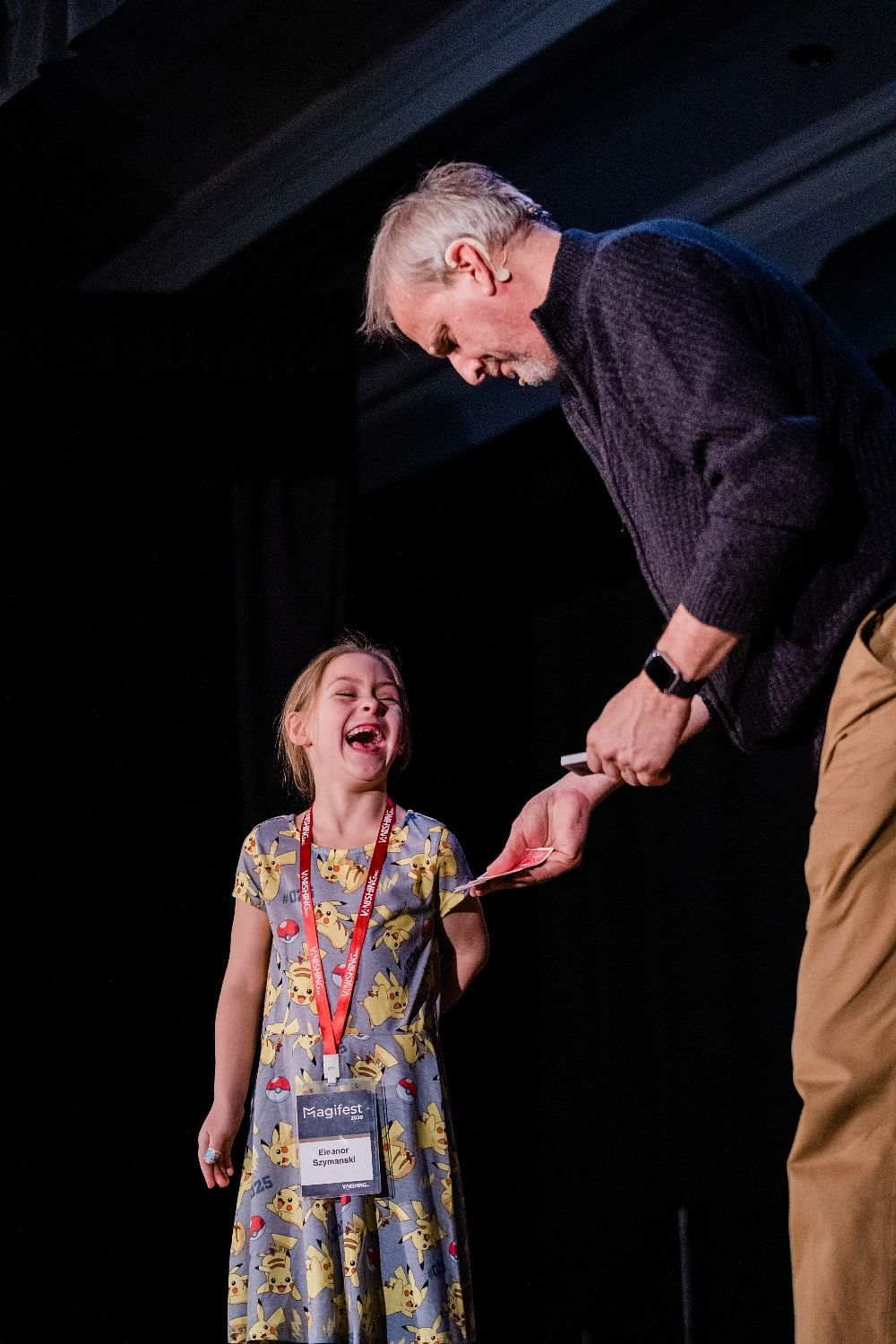 A young girl in a Pikachu dress has a huge smile on her face after seeing magician David Williamson perform a card trick