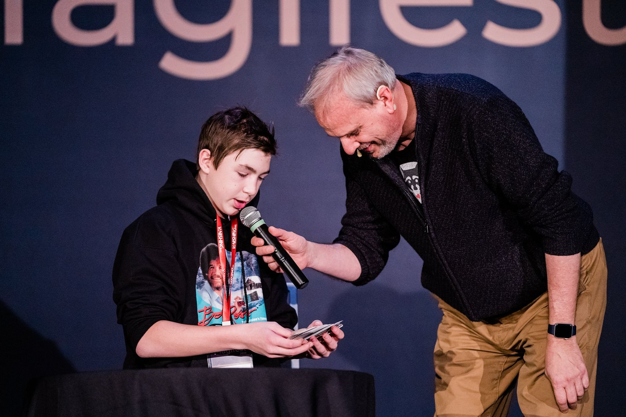 A young magician performs a card trick for magician David Williamson at the Magifest Magic Convention