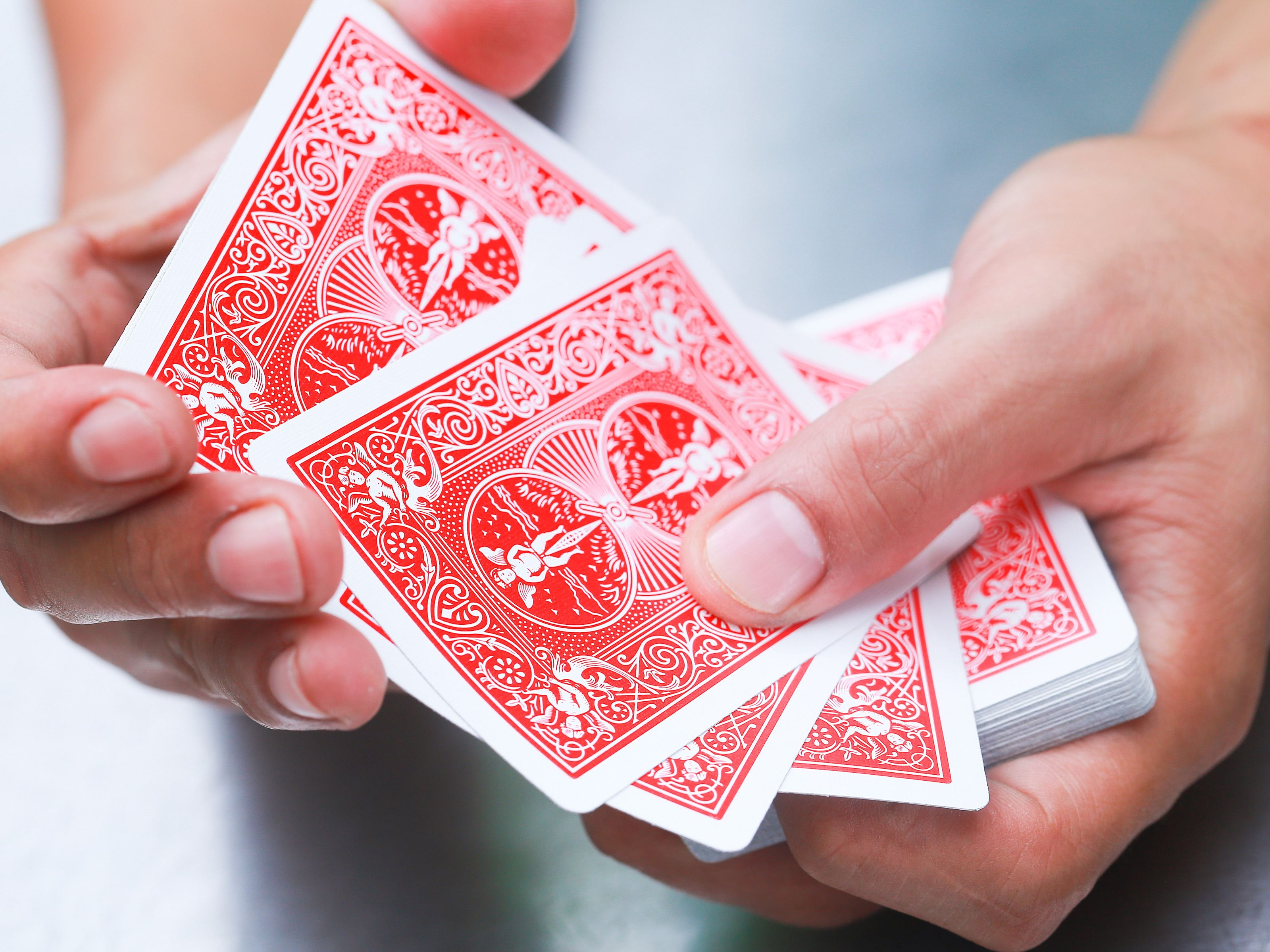 Beginner magician use red Bicycle playing cards to perform an easy card trick