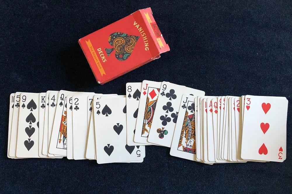 A red jack of diamonds is sandwiched between two black playing cards in a Dapper Deck from Vanishing Inc
