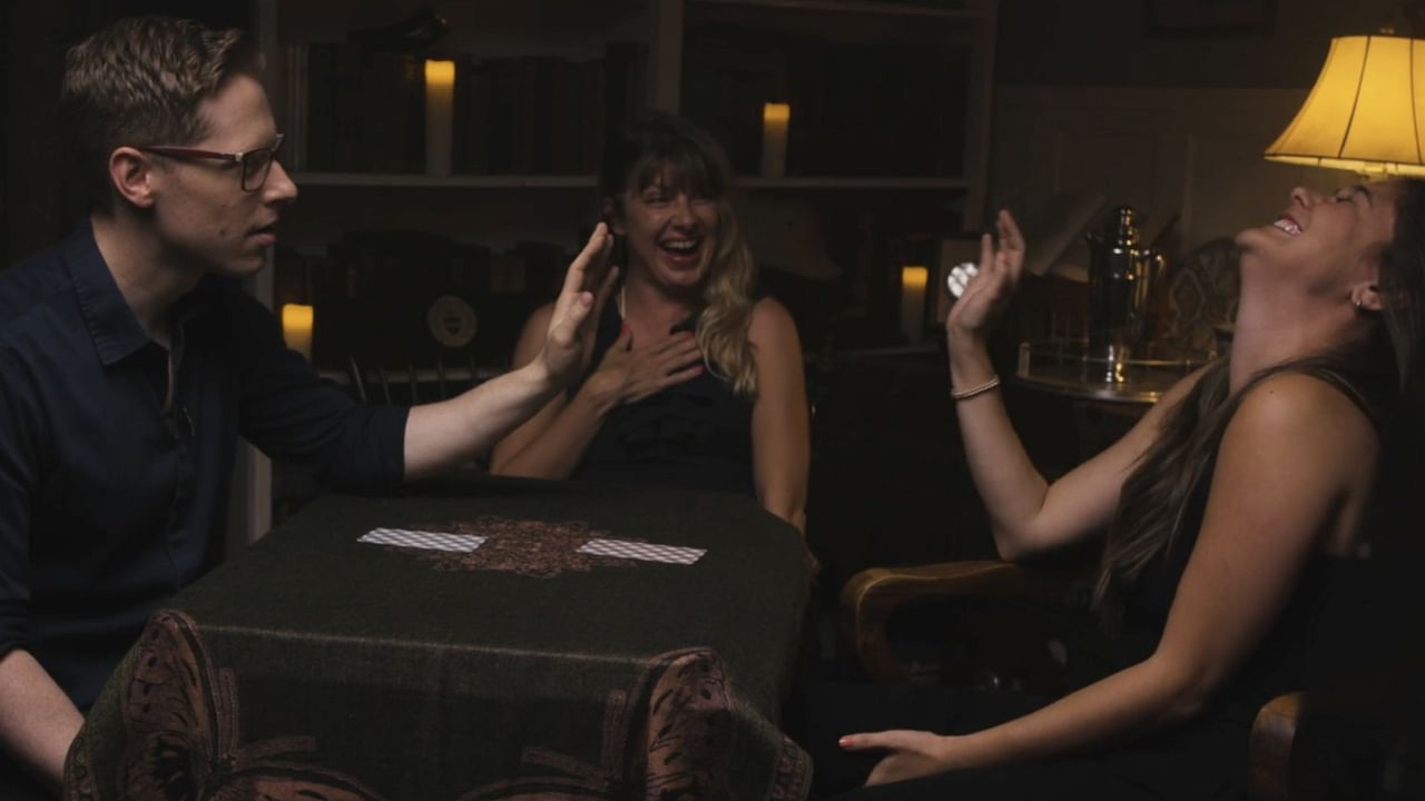 Two women laughing and smiling as magicain Ben Seidman performs The Oracle System mentalist trick for them