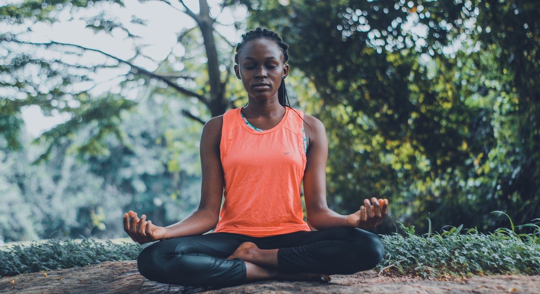 Woman meditates in the woods while practicing mindfulness
