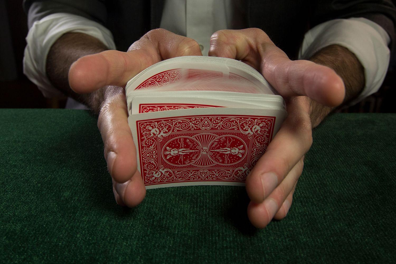 Card mechanic executes a False riffle shuffle to cheat at cards