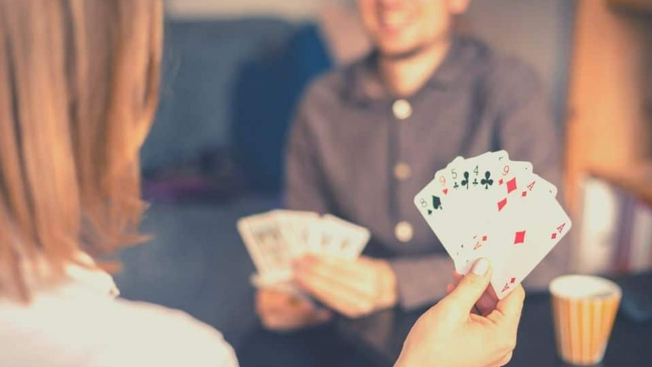A couple plays a fun card game on game night