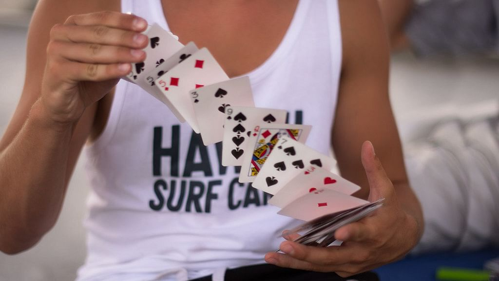 Man in tank top performs card spring card flourish with deck of cards