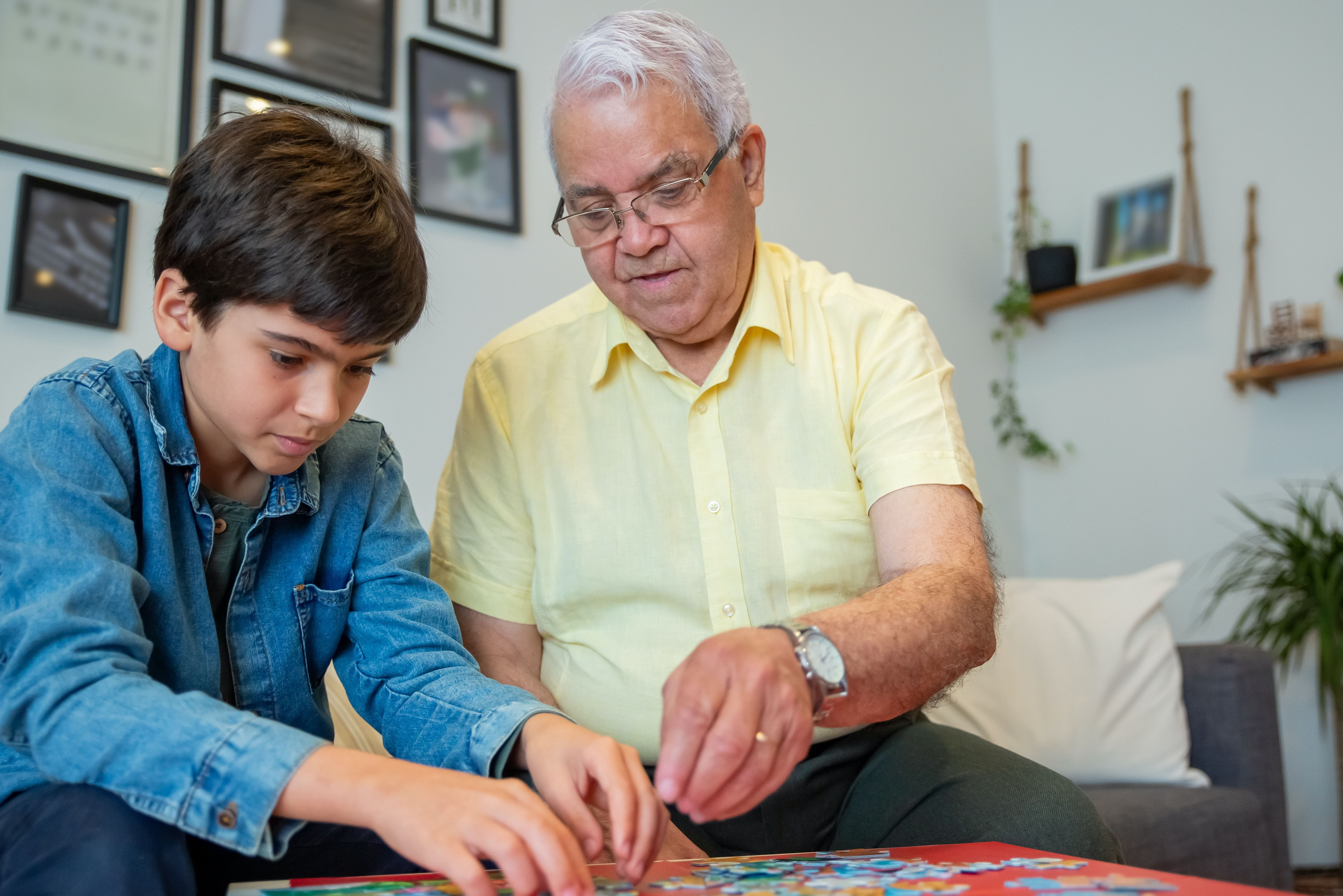 A young child and his grandfather play with a jigsaw puzle