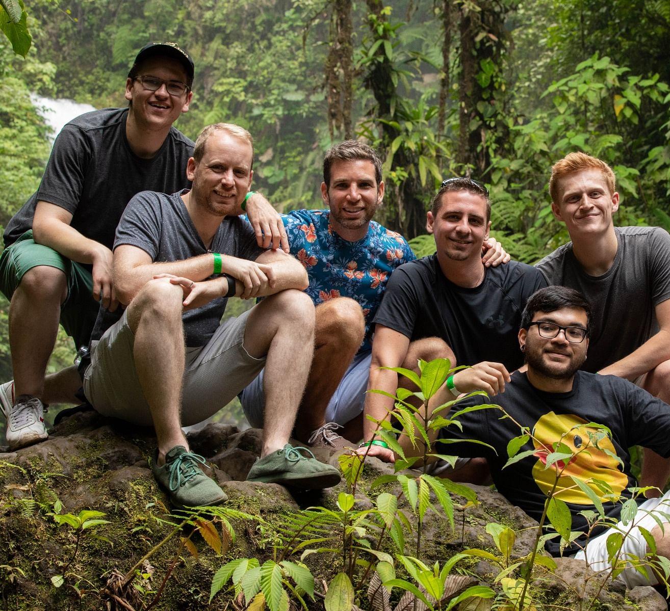 Members of the Vanishing Inc. Magic team pose near a waterfall in Costa Rica