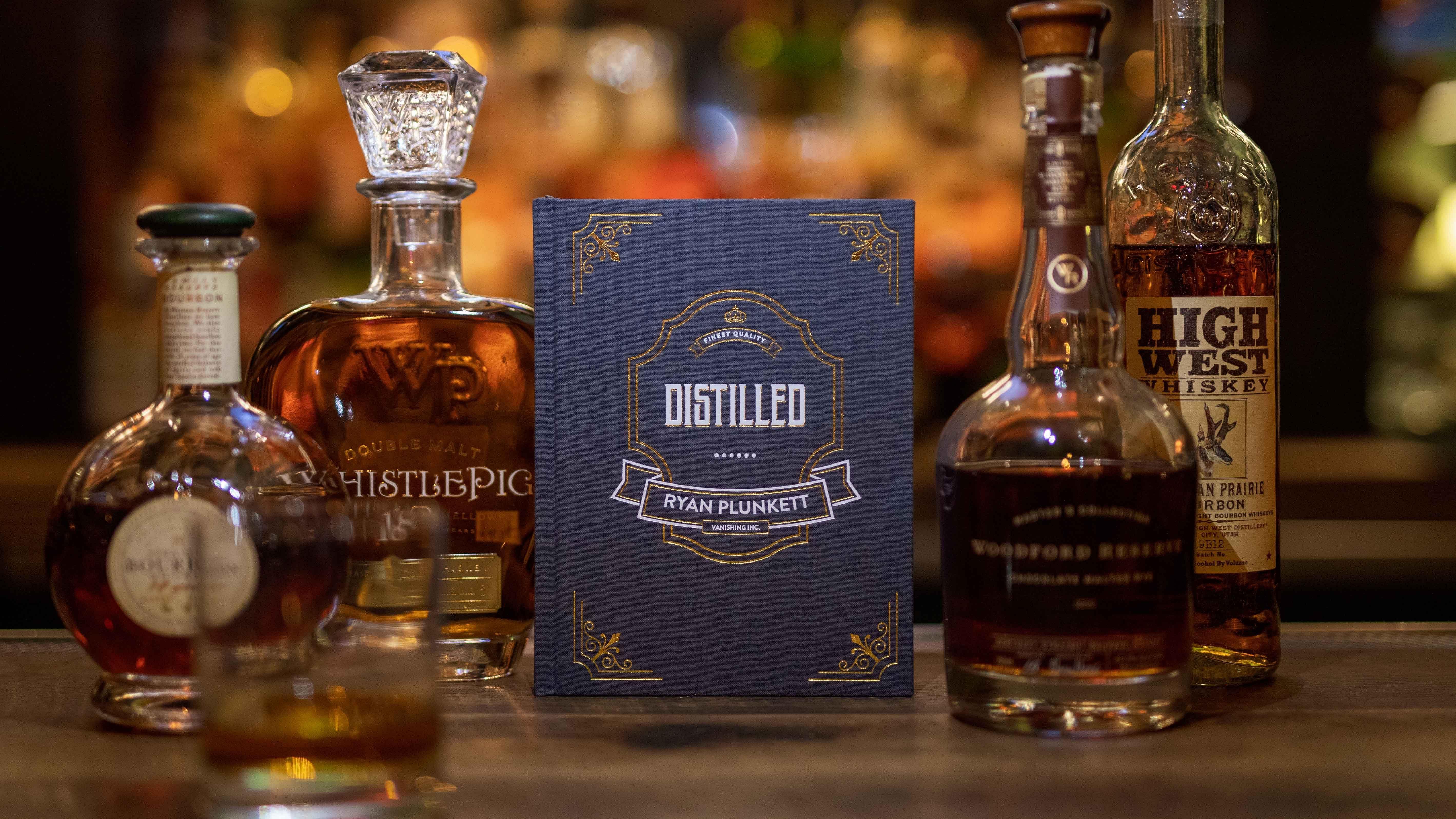 Magician Ryan Plunkett's book Distilled rests on a variety of liquor bottles