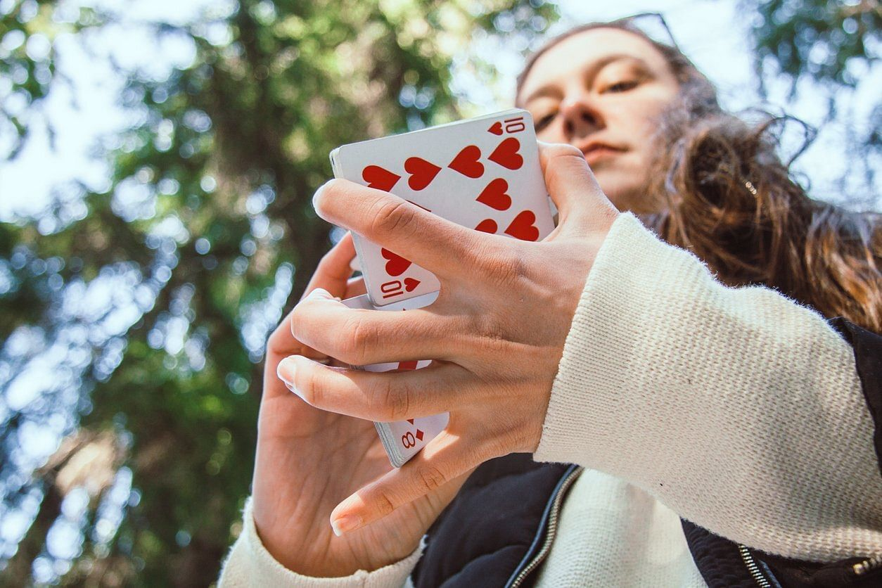 girl uses a deck of bicycle playing cards to do a card magic trick