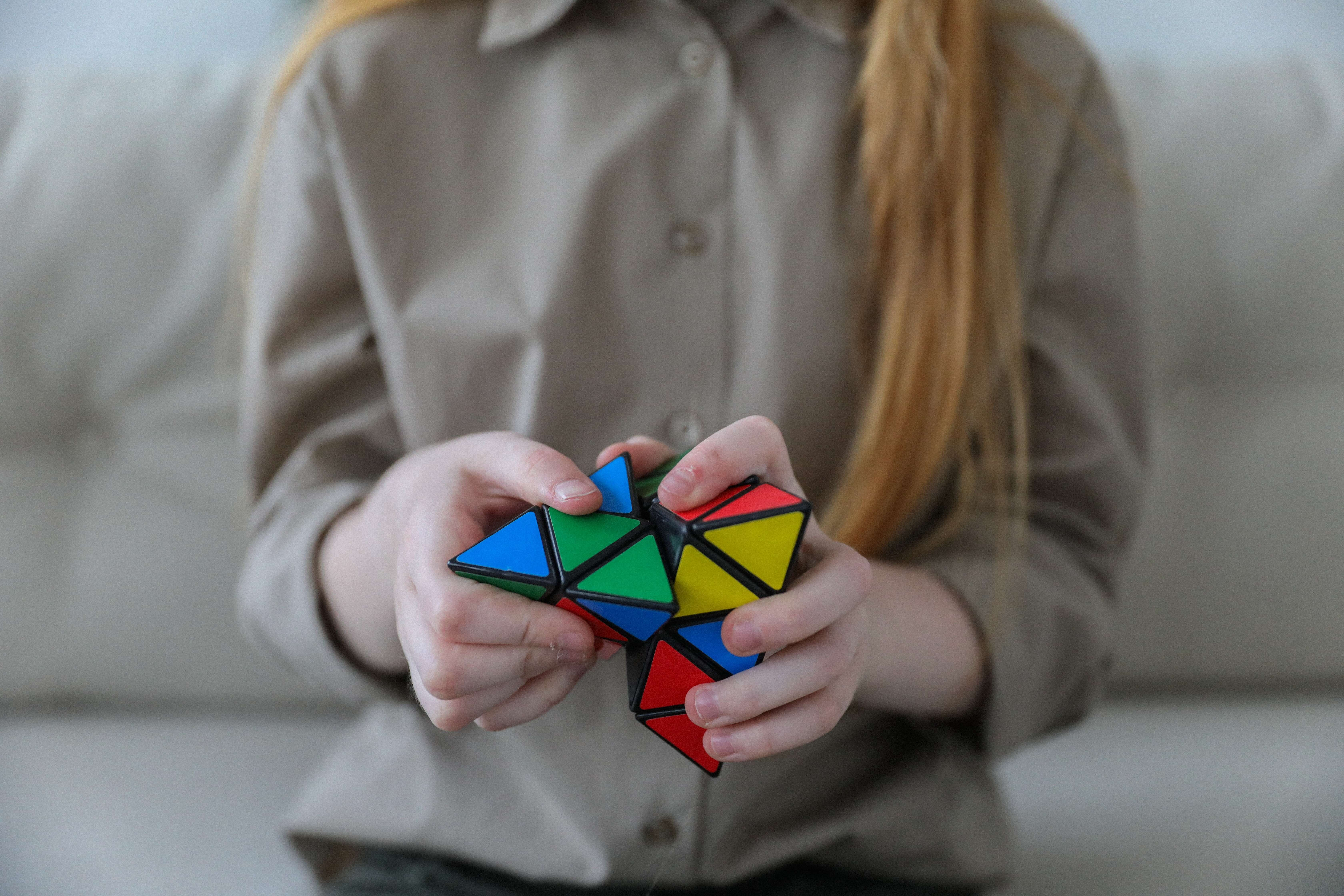 Girl with red hair plays with bright rubik's cube style puzzle brain teaser