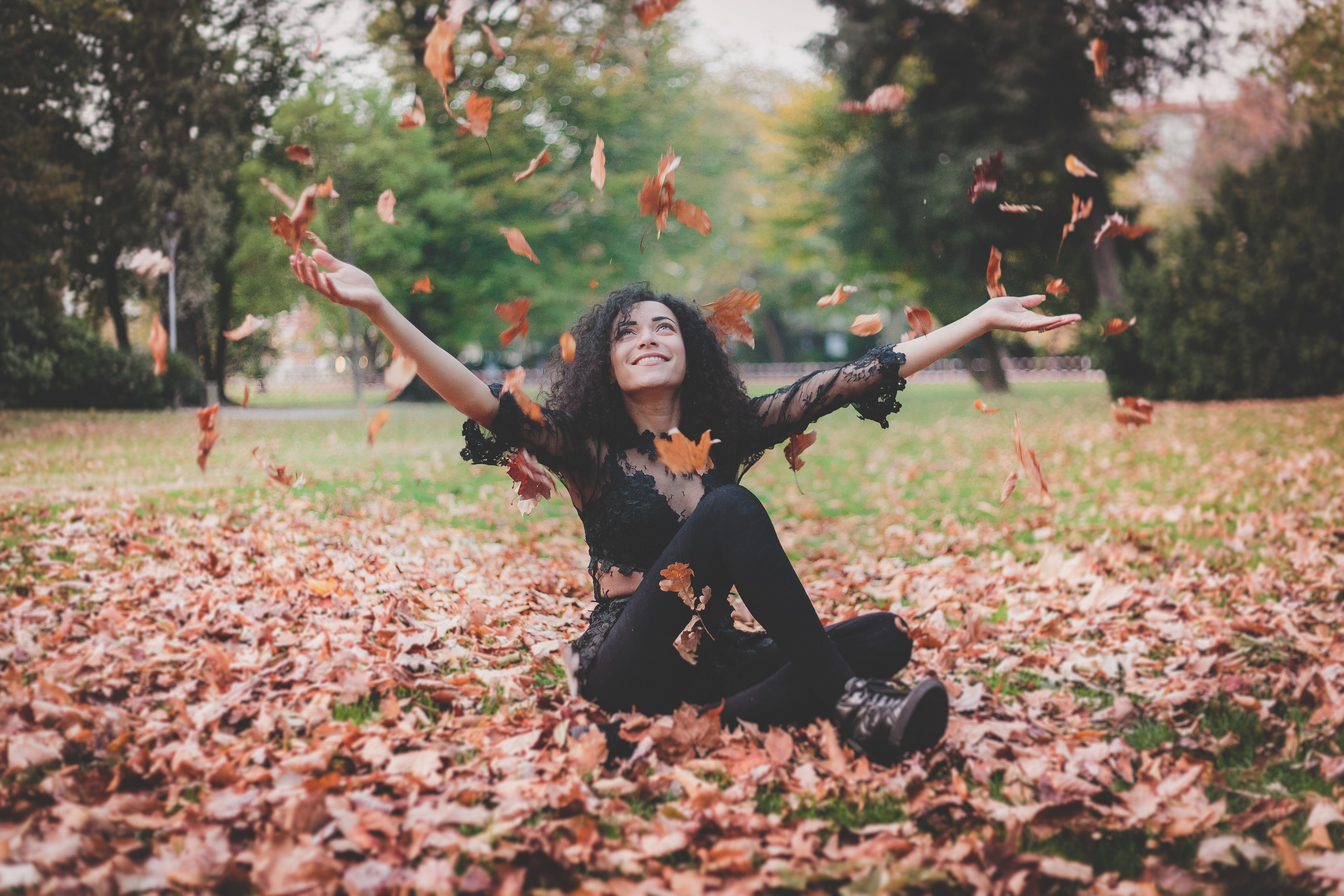 happy woman smiles while playing in a pile of leaves