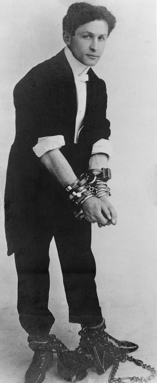 Black and White photo of Harry Houdini locked in a pair of handcuffs
