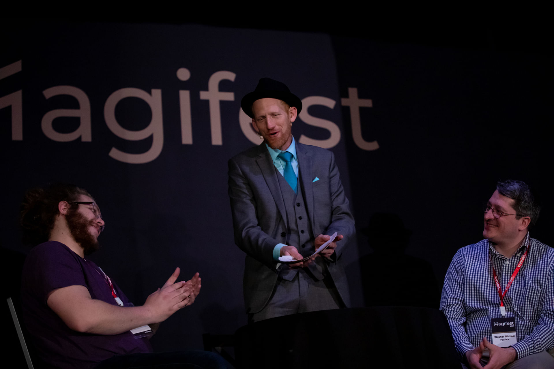 Magician in hat performs card trick on stage