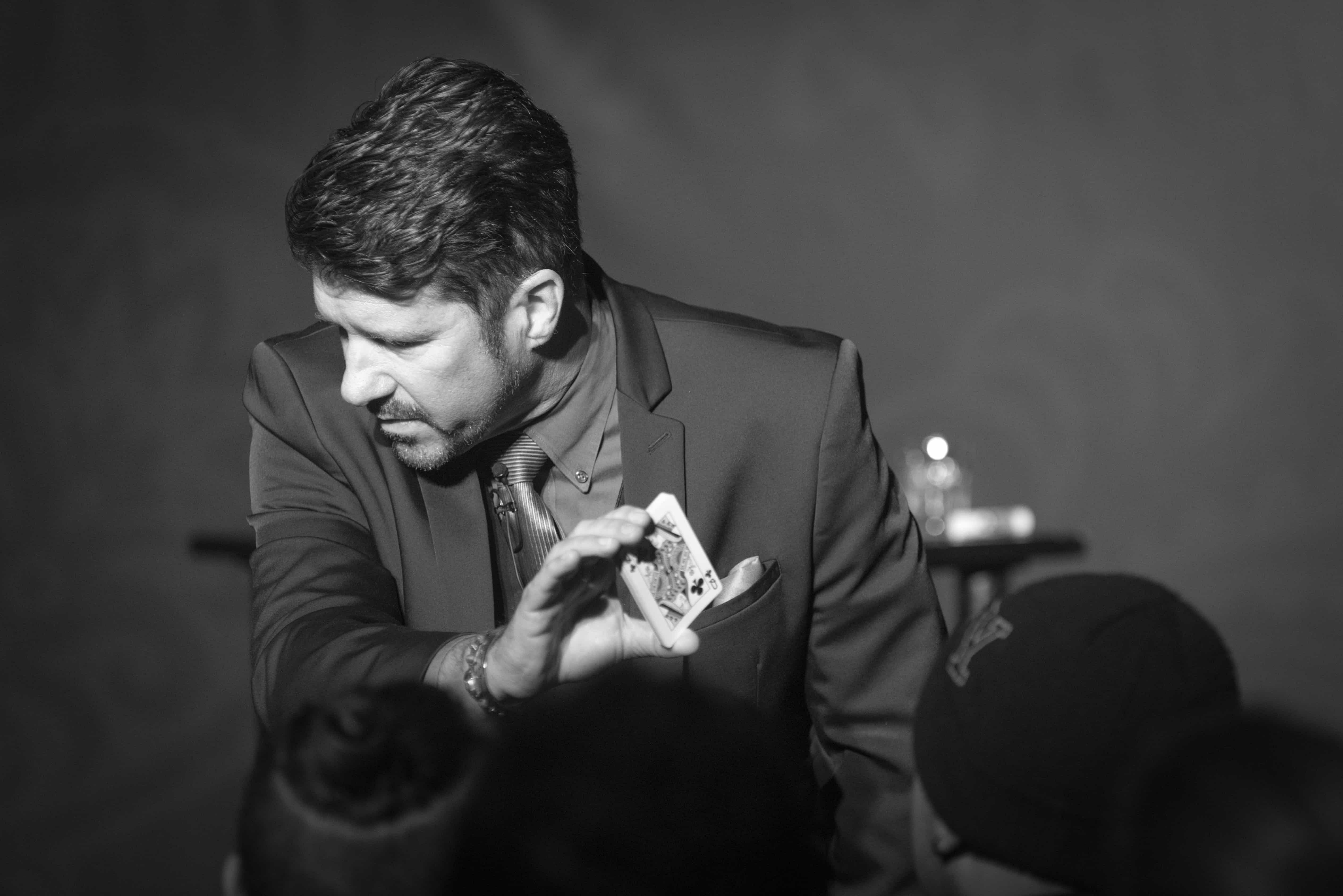 Mentalist Banachek shows a queen of clubs to the audience during a stage magic performance