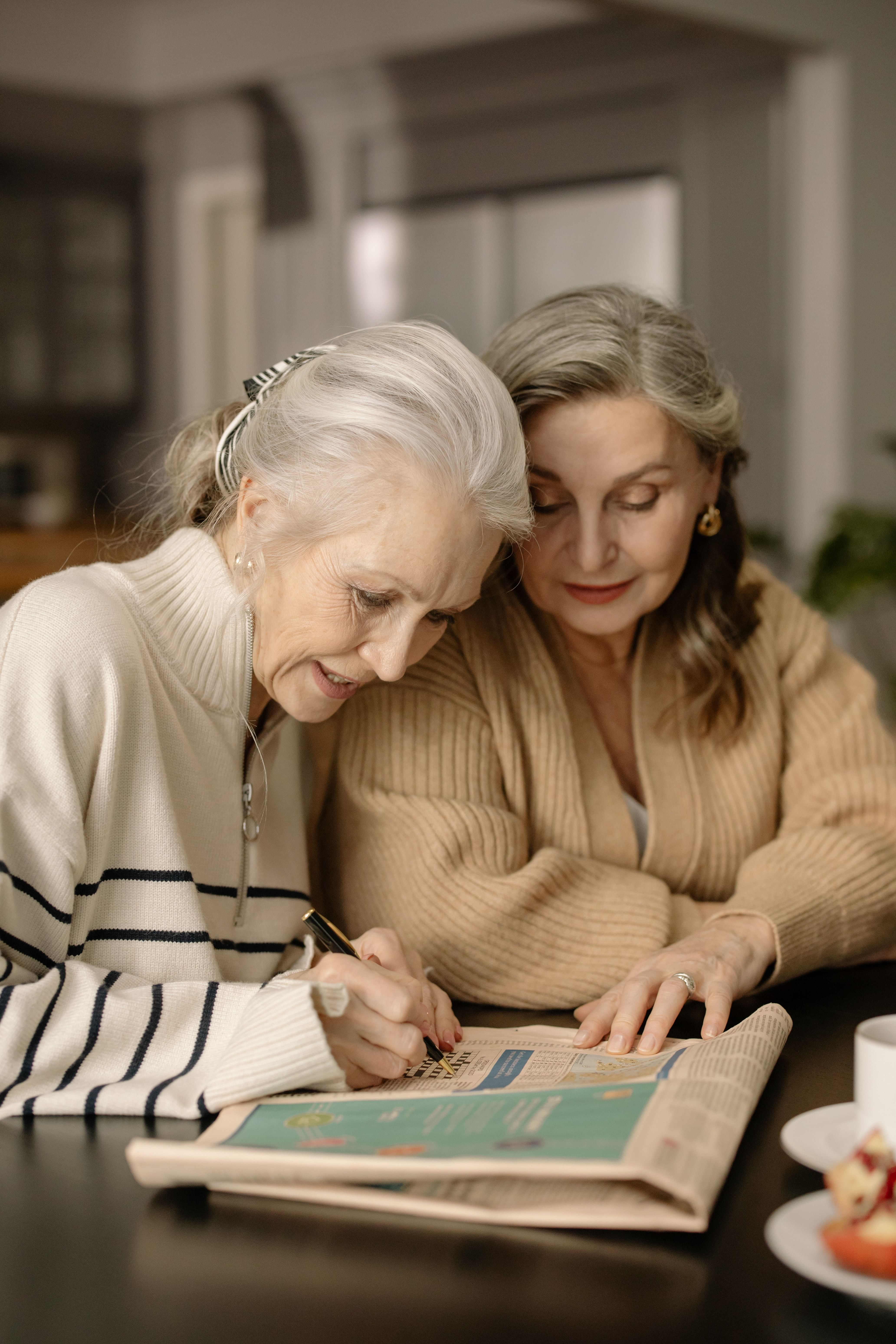 Two older elderly woman play a crossword puzzle at the table