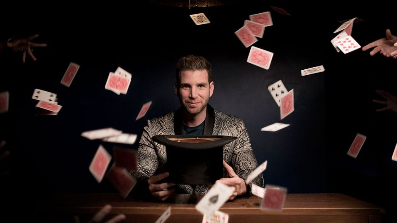 magician sits in front of a black hat as playing cards fly everywhere in a mess
