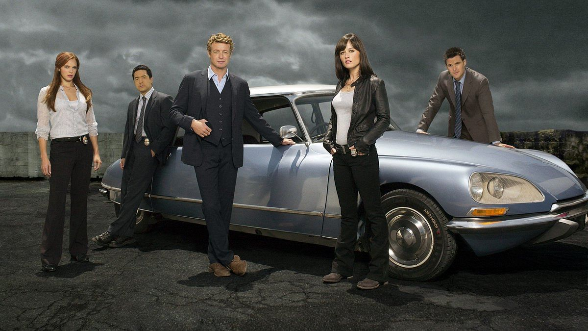 The Mentalist cast poses in front of an antique car with Patrick Jane, who is played by Simon Baker, in front